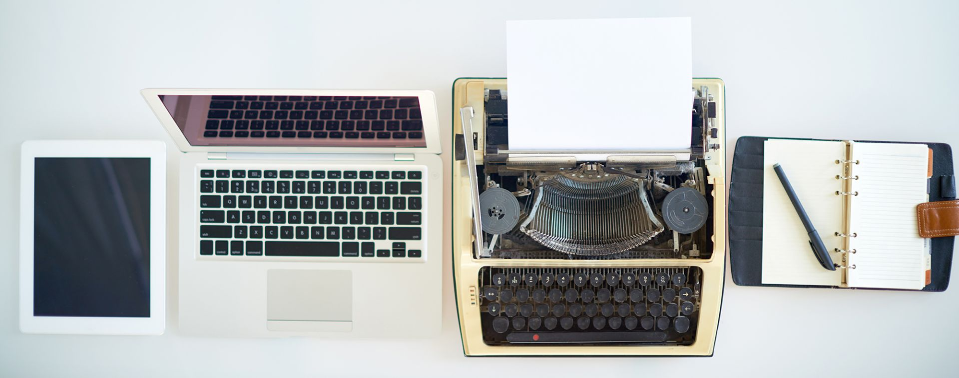 High angle view of diary with pen, typewriter, laptop and tablet in a row